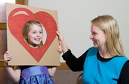 Little girl with heart cutout around her face held up by a teacher