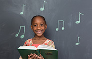 Girl holding a hymn book with music notes on a chalkboard behind her