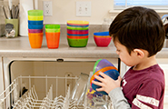 Young boy unloading a dishwasher