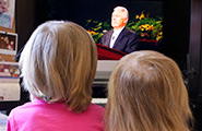 Two little girls watching General Conference on TV