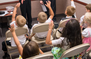 Primary children raising their hands in class