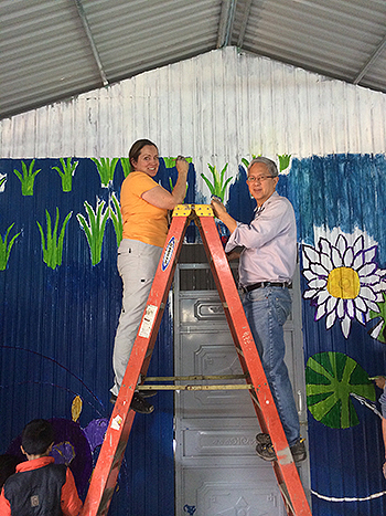 Elder Gerrit W. Gong and his wife, Susan, participate in a Christmas mural project in Vietnam. Photo courtesy of the Gong family.