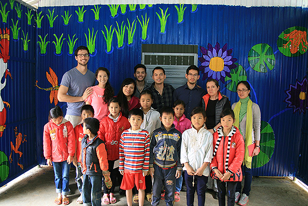 Members of Elder Gerrit W. Gong's family stand in front of a mural project with the children who assisted them in Vietnam. Photo courtesy of the Gong family.
