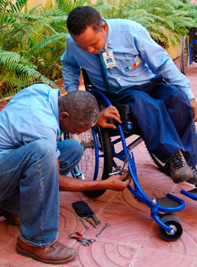 man fixing a wheelchair