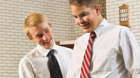 rapaz ajudando outro a distribuir o sacramento
