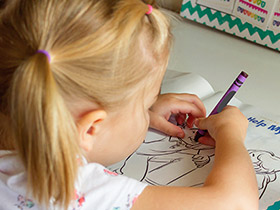 young girl coloring picture