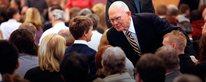Elder Oaks shaking hands with a young man