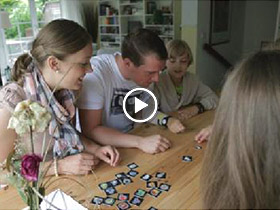 family playing a game on kitchen table