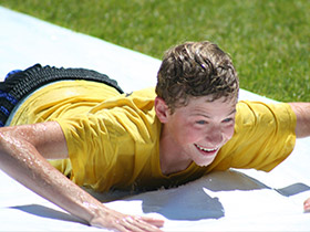 youth sliding on water slide