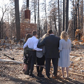 family looking at burnt home