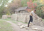 An image of a man on a road building a stone wall.