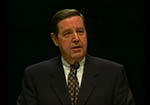 A younger Elder Jeffrey R. Holland stands speaking at a microphone in front of a black background.