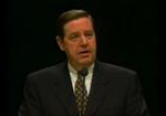 Elder Holland stands speaking with a black background behind him.
