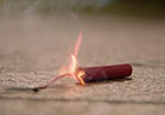 A picture of a red firecracker lit and lying on the ground.