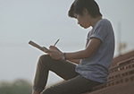 A young man sits writing in a large notebook.