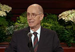 A picture of President Henry B. Eyring smiling at the pulpit in General Conference.
