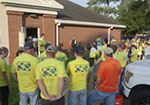 A group of LDS volunteers in yellow Helping Hands shirts stand outside of a building.