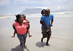 A man and woman walk along the beach with kids on their backs, smiling.