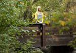 A woman stands on a wooden bridge in the woods.