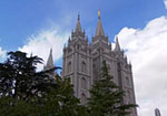 A picture of the Salt Lake Temple with trees in the foreground and a blue sky with clouds behind it.