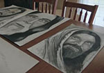 Sketches of Jesus Christ are spread out across a table.