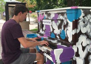 A man plays a colorfully painted piano outside.