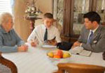 A young man sits with his grandmother and a priesthood leader at the dining room table.