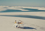 A person sits at a white grand piano in the middle of white sand dunes.