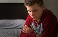 young man praying beside his bed