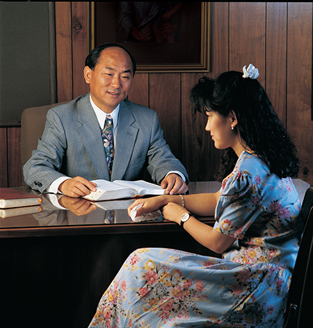 young woman and bishop at his desk