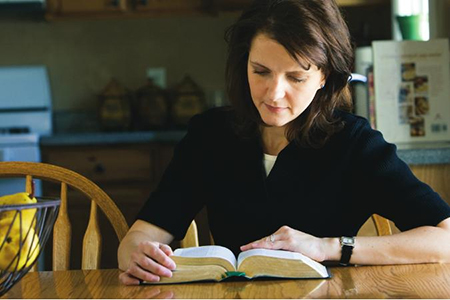 teacher preparing with scriptures and manual