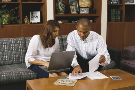 couple with computer and papers