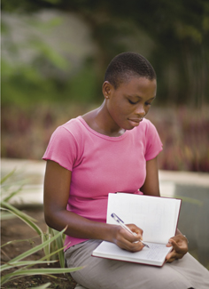 young African woman writing in journal