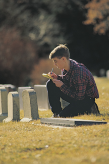 young man next to headstones