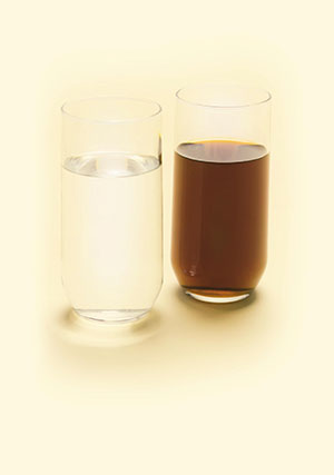 two glasses, one containing clean water and one containing dirty water
