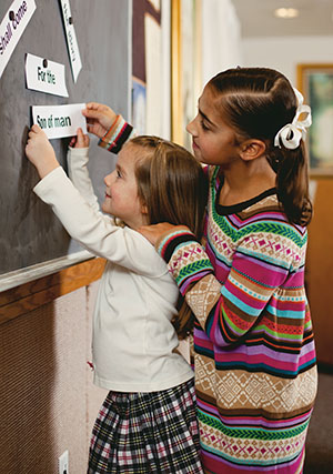 two girls putting word strips on chalkboard