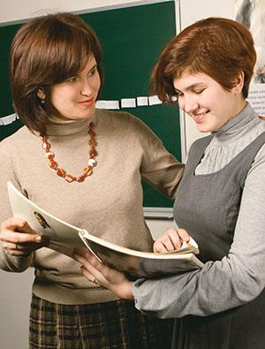 two Primary leaders looking at Gospel Art Book