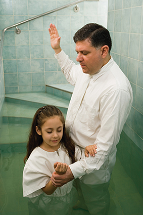 father baptizing child