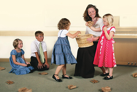 children around teacher with basket