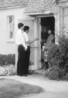 Two missionaries at the door of an investigator
