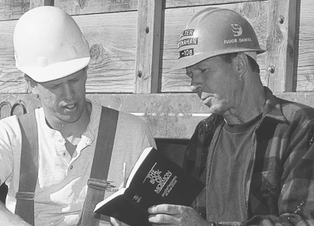 man in hard hat showing Book of Mormon to coworker