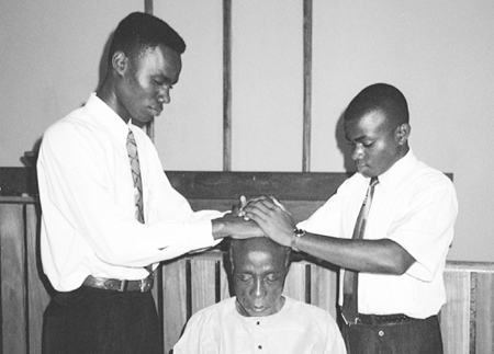 African priesthood holders giving a blessing
