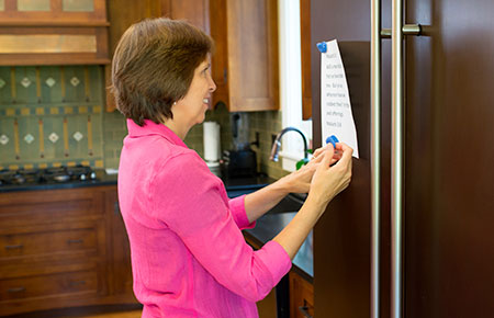 Sister Durrant putting scripture on refrigerator
