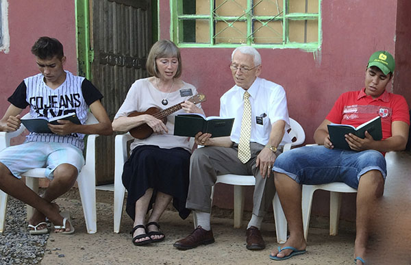 senior missionary couple with young women