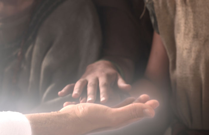 depiction of hand touching Savior's hand