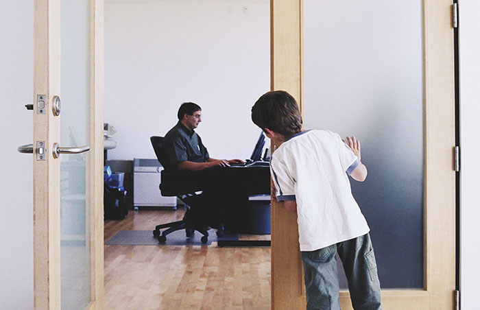 boy watching father from doorway of office