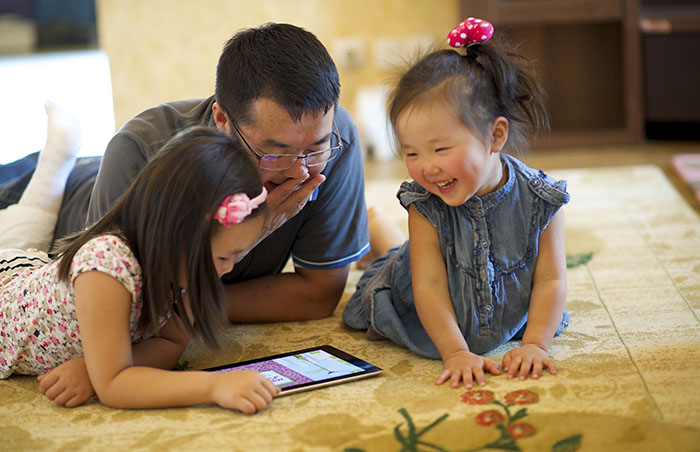 father and girls looking at tablet