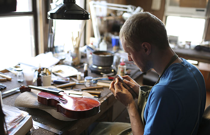 violin maker in workshop