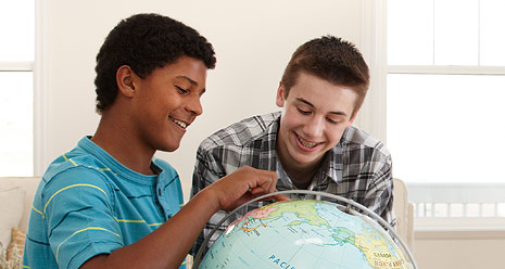 two young men looking at globe