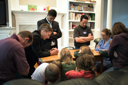 Missionaries praying with family
